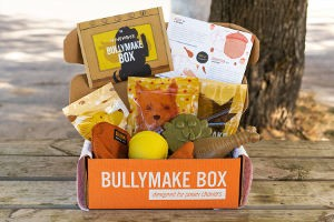 An open BullyMake Box filled with toys placed outside on wooden planks