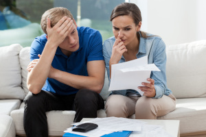 Concerned couple on couch reviewing a vet bill