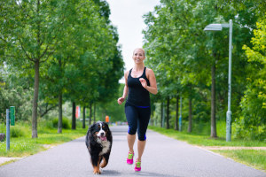 Woman jogger running with her dog in street