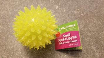 Yellow Gnawsome squeak and light ball sitting on table
