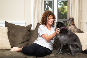 Woman pet sitter holding dog on couch