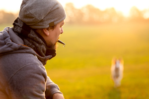 Man using dog whistle in field