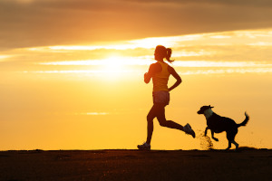 Woman running with dog at beach at sunset