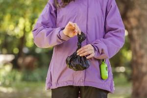 Woman holding a black dog poop bag