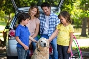 Happy family with dog getting ready for road trip